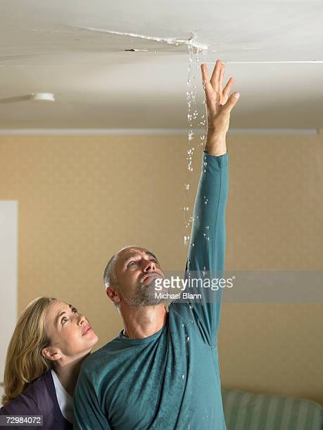 Mid adult woman next to mature man reaching up to touch water falling from crack in ceiling