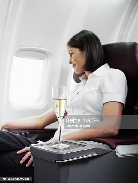 Mid adult woman on airplane, looking through window