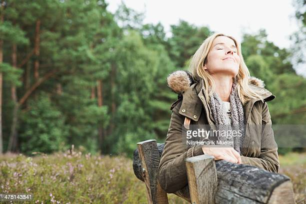 Mid adult woman on bench with eyes closed
