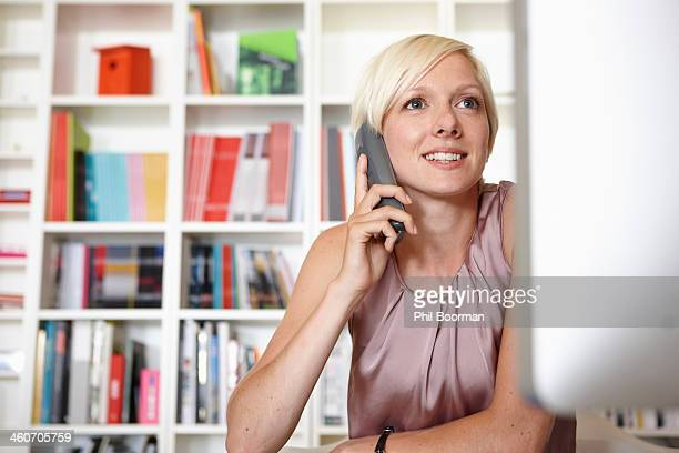 Mid adult woman on landline phone