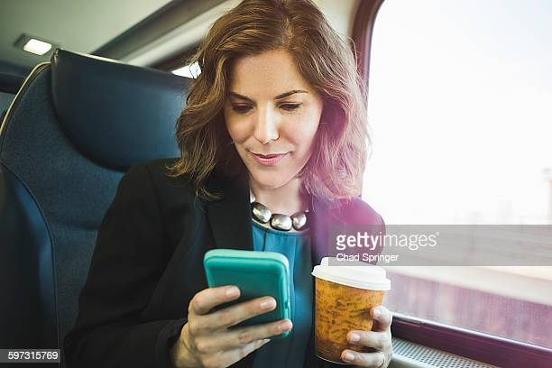 Mid adult woman on train, using smartphone, holding coffee cup