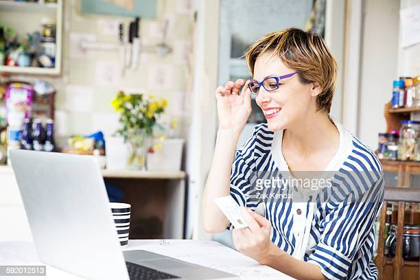 Mid adult woman online shopping in kitchen