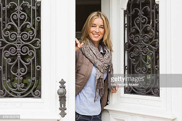Mid adult woman opening front door