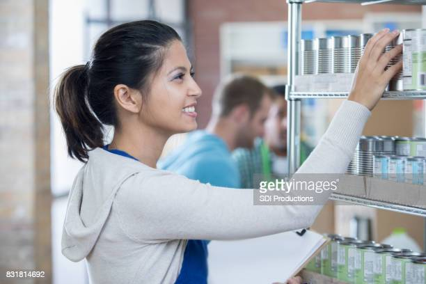 Mitte Erwachsene Frau organisiert konservierte Lebensmittel in Essen bank