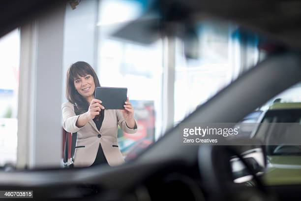 Mid adult woman photographing car in showroom