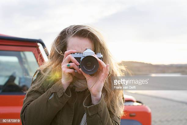 Mid adult woman photographing with SLR in coastal parking lot