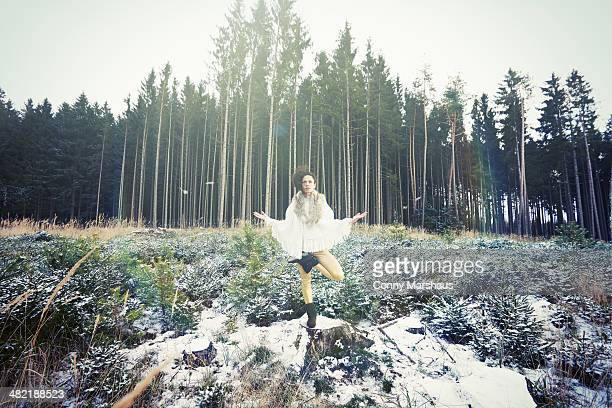 Mid adult woman practicing standing tree yoga pose in forest