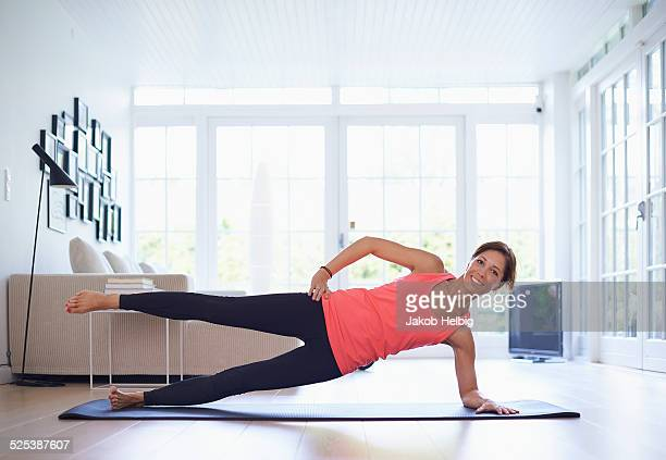 Mid adult woman practicing yoga position in living room