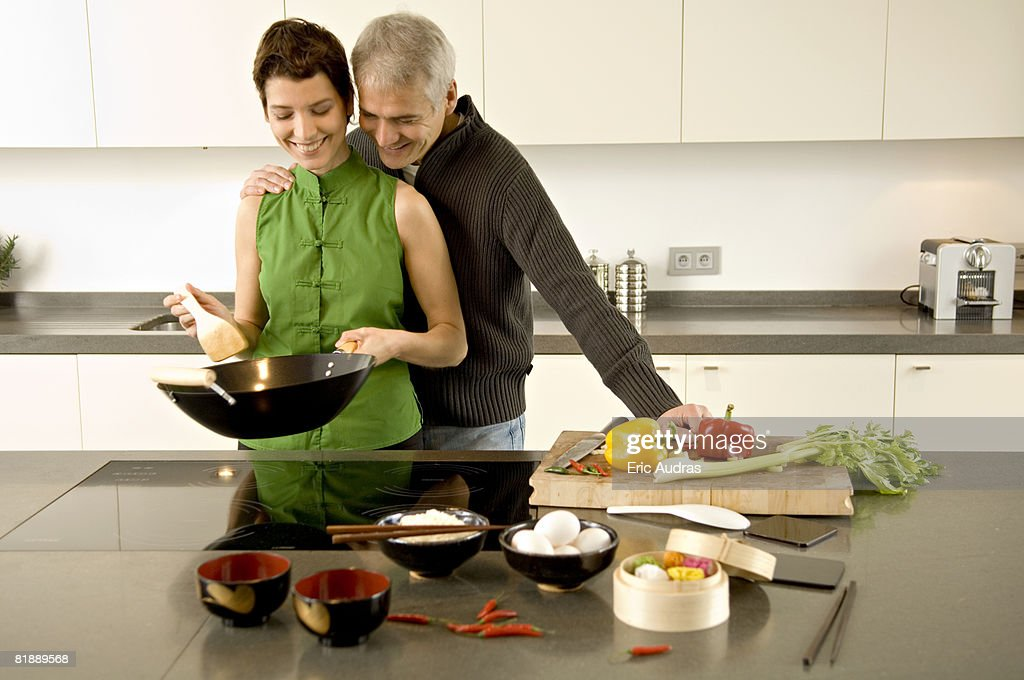 Mid adult woman preparing food with a mature man standing with arm around her in the kitchen : Stock Photo