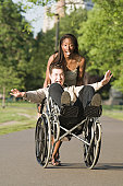 Woman pushing a disabled man sitting in a wheelchair