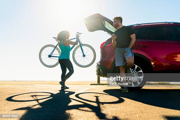 Mid adult woman putting bicycle into car boot