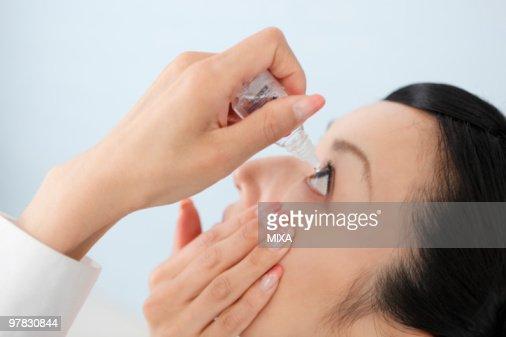 Mid adult woman putting eye-drops