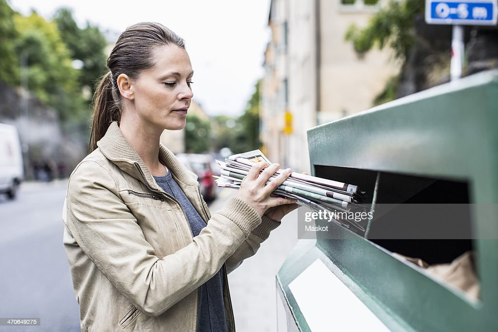 Mid adult woman putting newspapers into recycling bin