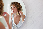 Mid adult woman putting on earrings in mirror