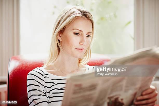 Mid adult woman reading newspaper