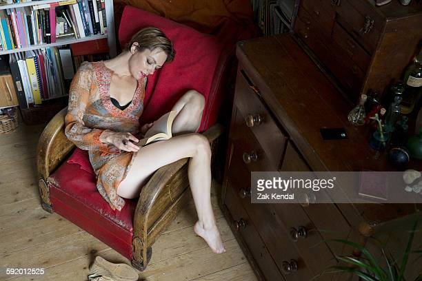 Mid adult woman reclining in retro armchair reading a book