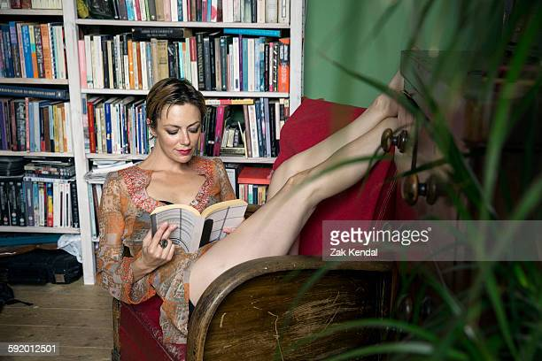 Mid adult woman reclining in retro armchair with feet up reading a book