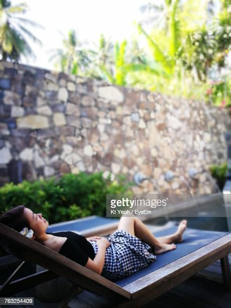 Mid Adult Woman Relaxing On Deck Chair At Poolside