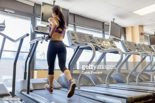 Mid adult woman running on treadmill in gym