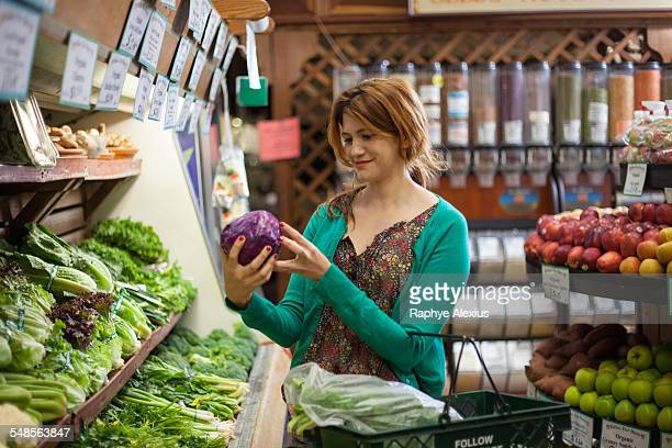 Mid adult woman selecting red cabbage in health food store