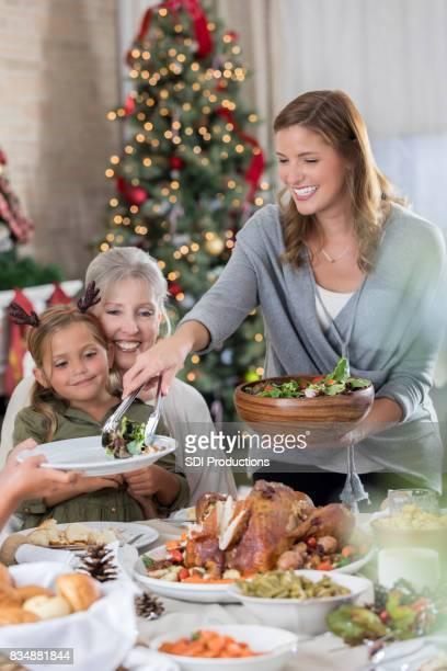 Mitte Erwachsene Frau serviert Salat zum Weihnachtsessen