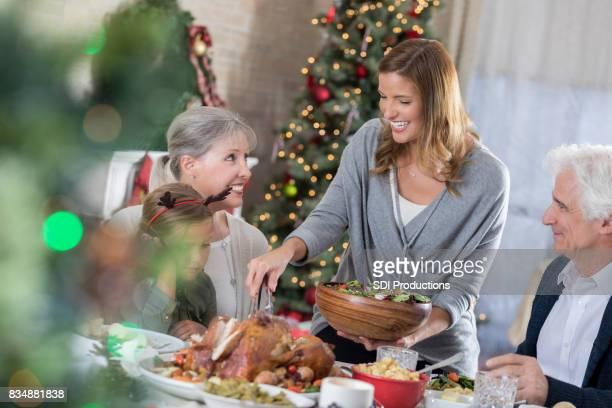 Half volwassen vrouw serveert salade tijdens familie kerstdiner