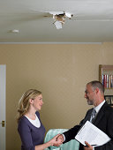 Mid adult woman shaking hands with mature man holding clipboard beneath hole in ceiling