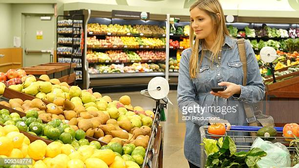 Mid adult woman shops for fresh fruit in supermarket