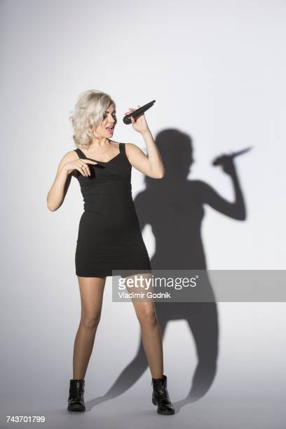 Mid adult woman singing with microphone while standing against white background