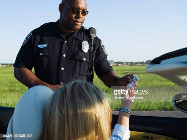 Mid adult woman sitting in a convertible car giving her driving license to a police officer