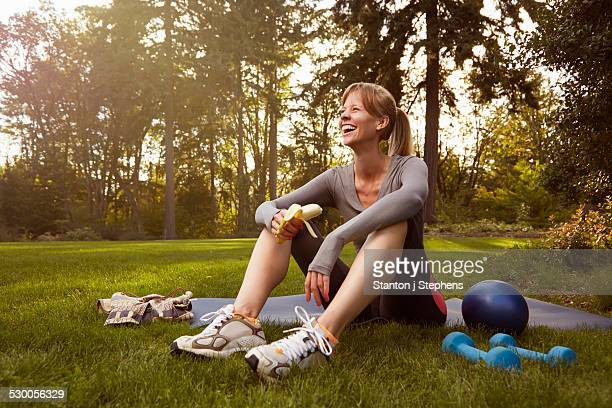 Mid adult woman sitting in park taking exercise break
