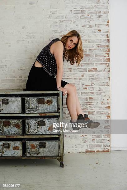 Mid adult woman sitting on metal dresser
