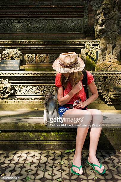 Mid adult woman sitting on steps, monkey sitting beside her, Ubud, Bali, Indonesia