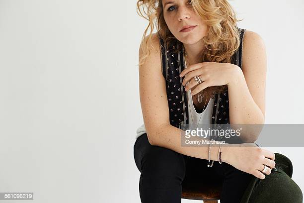 Mid adult woman sitting resting elbow on knee