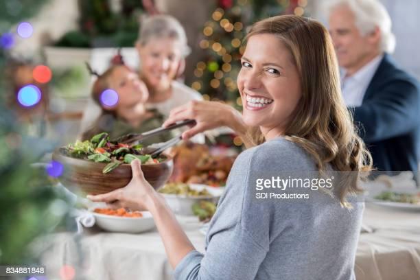Mid volwassen vrouw glimlacht voor camera tijdens familie kerstdiner