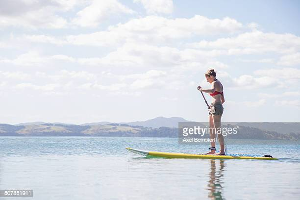 Mid adult woman stand up paddleboarding at sea