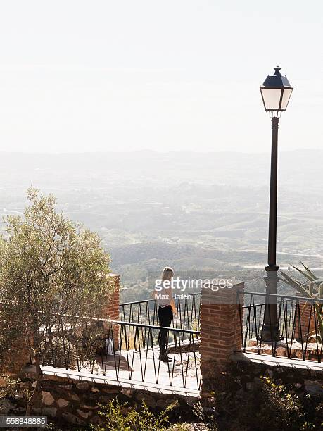 Mid adult woman standing on balcony, looking at view, Mijas, Andalucia, Spain