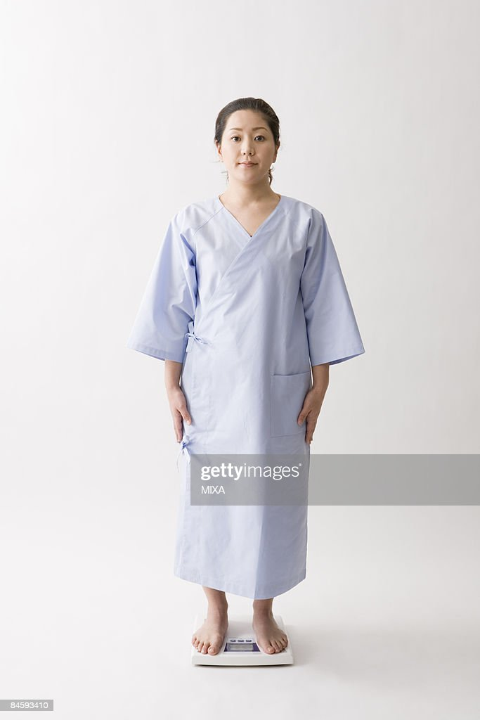 Mid adult woman standing on bathroom scale
