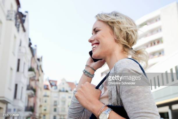 Mid adult woman strolling in city making smartphone call