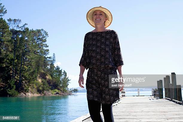Mid adult woman strolling on pier, New Zealand