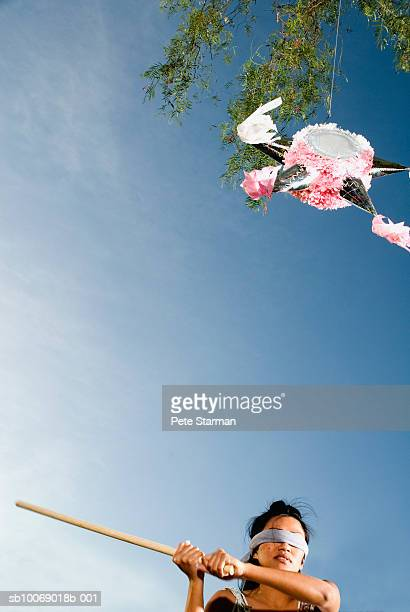 Mid adult woman swinging stick at pinata hanging from tree