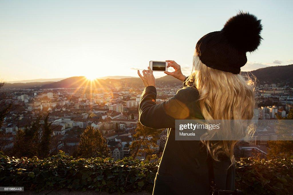 Mid adult woman taking photo on phone, Graz, Styria, Austria