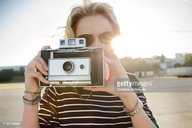 Mid adult woman taking photographs on vintage camera