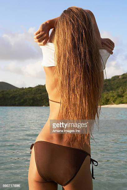 Mid Adult Woman Taking T-Shirt Off in Ocean