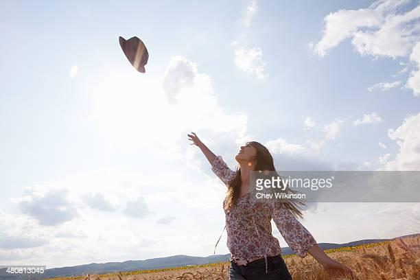 Mid adult woman throwing hat in air