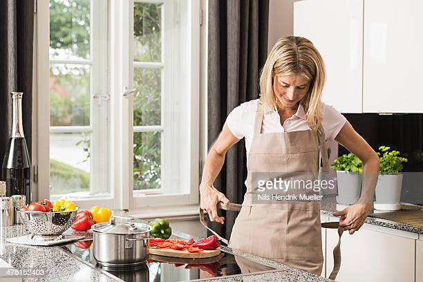 Mid adult woman tying apron in kitchen