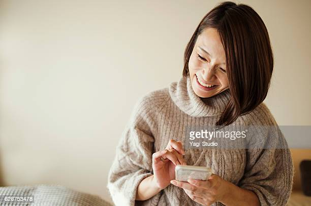 Mid adult woman using a smart phone in bed room