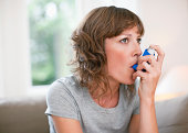 Mid adult woman using asthma inhaler