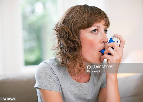 Mid adult woman using asthma inhaler
