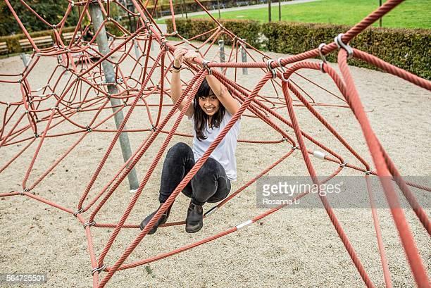 Mid adult woman using climbing ropes, smiling at camera
